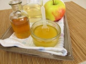 На столе пиала с медом, яблоко и укус